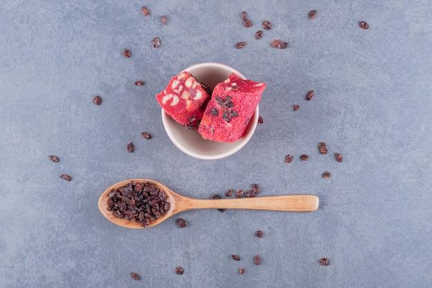 Turecka rozkosz - lokum z suchą rodzynką na szarym tle.