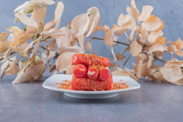 Turecka rozkosz rahat lokum z pistacjami na białym talerzu.