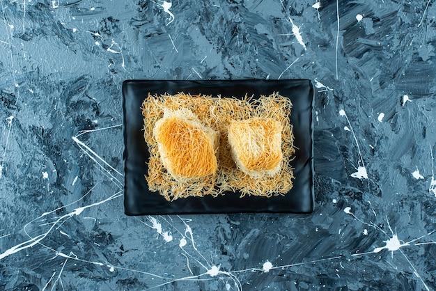 Turecki deser kadayif na czarnej płycie, na niebieskim stole.