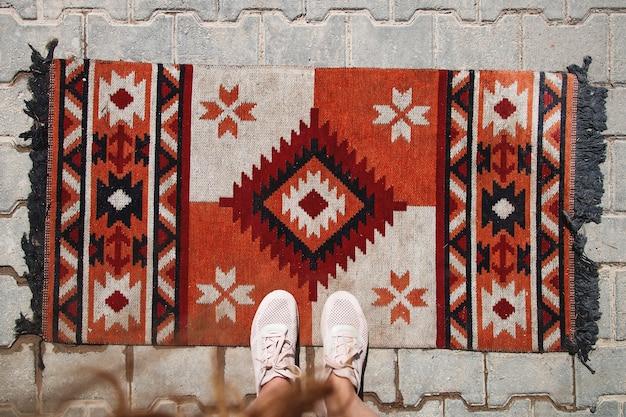 Turecki dywan na podłodze na zewnątrz, a kobiece stopy na nim podróż do kultury wschodniej autentyczne zdjęcie