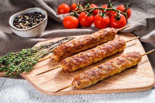 Turecki i arabski tradycyjny kebab na desce do krojenia, mielona wołowina, mięso jagnięce. białe tło.