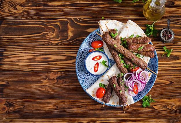 Turecki i arabski tradycyjny ramadan mix talerz kebab kebab adana, kurczak, jagnięcina i wołowina na chlebie lavash z sosem. widok z góry