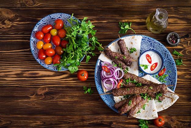 Turecki i arabski tradycyjny ramadan mix talerz kebab kebab adana, kurczak, jagnięcina i wołowina na chlebie lavash z sosem.