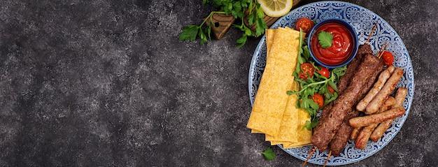 Turecki i arabski tradycyjny ramadan wymieszać talerz kebab. kebab adana, jagnięcina i wołowina na chlebie lavash z sosem pomidorowym. widok z góry