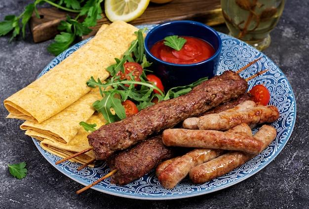 Turecki i arabski tradycyjny ramadan wymieszać talerz kebab. kebab adana, jagnięcina i wołowina na chlebie lavash z sosem pomidorowym.