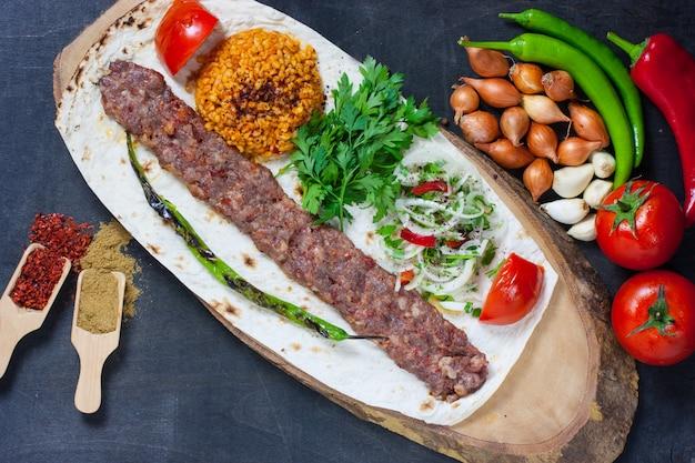 Turecki kebab adana z warzywami na talerzu