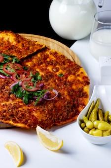 Turecki lahmajun do pizzy przyozdobiony pomidorowymi krążkami cebuli i natką pietruszki