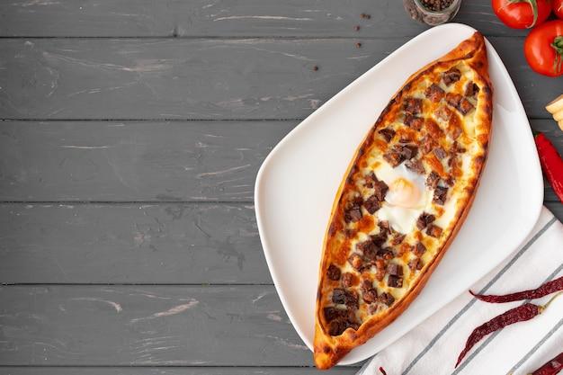 Turecki nadziewany chleb pide na szarym drewnianym stole