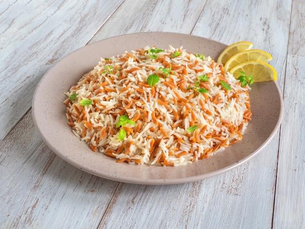 Turecki ryżowy pilaw z orzo w talerzu na białym drewnianym tle