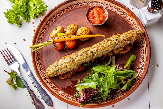 Turecki tradycyjny mix kebab z pieczonymi warzywami, pieczarkami i sosem pomidorowym, widok z góry, orientacja pozioma