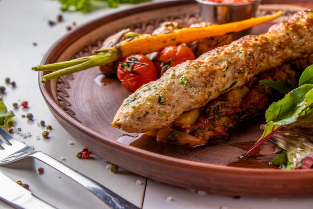 Turecki tradycyjny mix kebabu z pieczonymi warzywami, grzybami i sosem pomidorowym, orientacja pozioma
