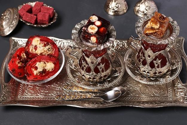 Tureckie armudy z herbatą i słodyczami na metalowej tacy na ciemnym tle, zbliżenie, format poziomy