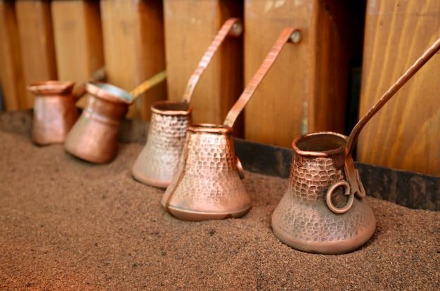 Tureckie bojlery do kawy umieszczone na gorącym piasku