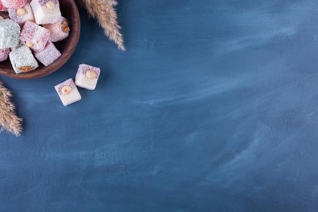 Tureckie lokum z orzechami laskowymi umieszczone w drewnianej misce.