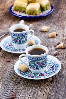 Tureckie przysmaki. kubki z czarną kawą i słodyczami