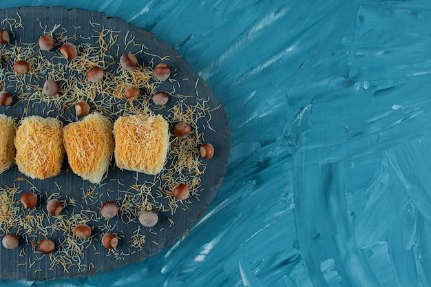 Tureckie przysmaki z orzechami makadamia na ciemnym drewnianym kawałku.