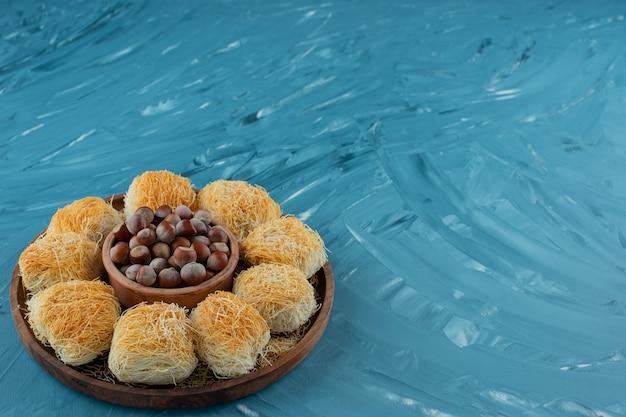 Tureckie przysmaki z orzechami makadamia na ciemnym drewnianym talerzu.