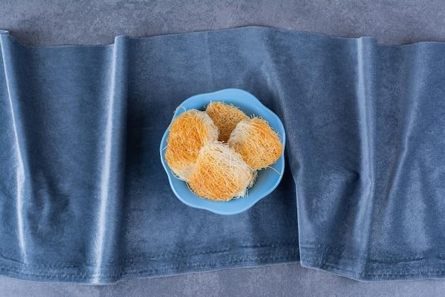 Tureckie słodkie desery w niebieskiej misce na kamieniu.