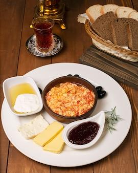 Tureckie śniadanie menemen z miodem, śmietaną, oliwkami, dżemem i odmianami sera w białym talerzu i szklance herbaty