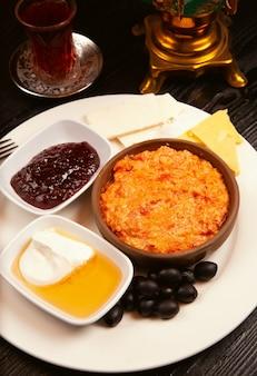 Tureckie śniadanie, menemen ze śmietaną, miodem, czarnymi oliwkami, dżemem, odmianami sera i szklanką herbaty.