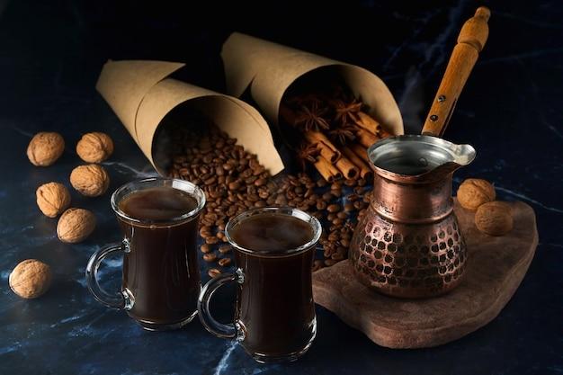 Turek i dwie filiżanki gorącej kawy z przyprawami, orzechami i ziaren kawy na ciemnym tle
