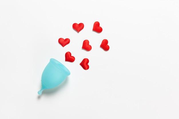 Turkusowa menstruacyjna filiżanka na białym tle z czerwonymi sercami
