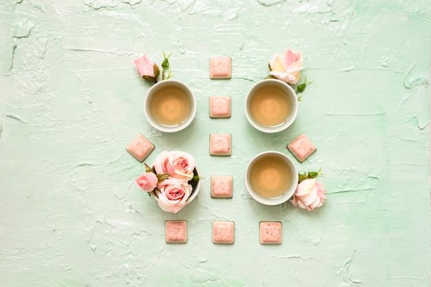 Turkusowe kubki z herbatą różaną, kwiatami róży, różową czekoladą na miętowej neo