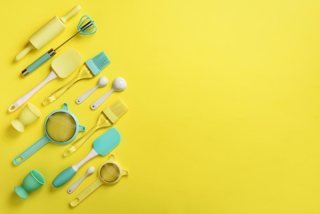 Turkusowe naczynia do gotowania na żółtym tle. składniki żywności.