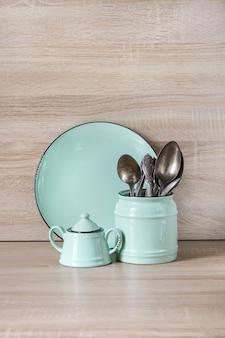Turkusowe naczynia, zastawa stołowa, przybory kuchenne i inne rzeczy na drewnianym blacie