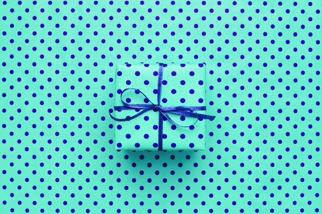 Turkusowe pudełko na niebieskim tle w kropki