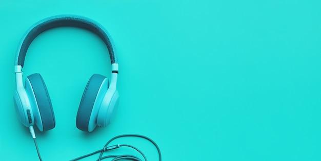 Turkusowe słuchawki na kolorowym tle. koncepcja muzyki z copyspace