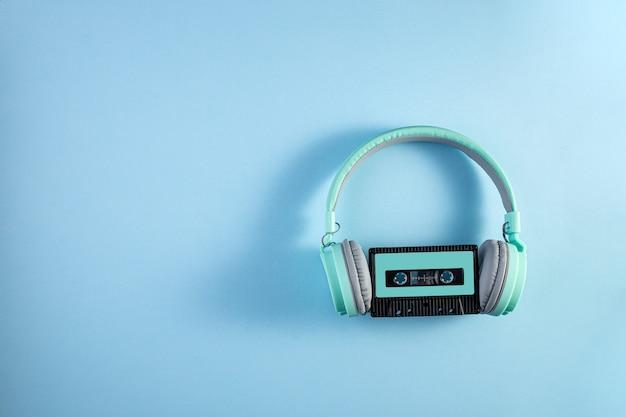 Turkusowe słuchawki z kasetą audio na niebieskim tle. koncepcja muzyki