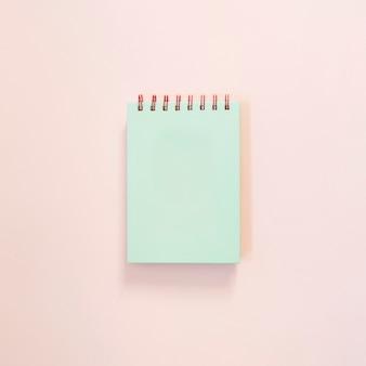 Turkusowy notatnik na jasnym tle różowy