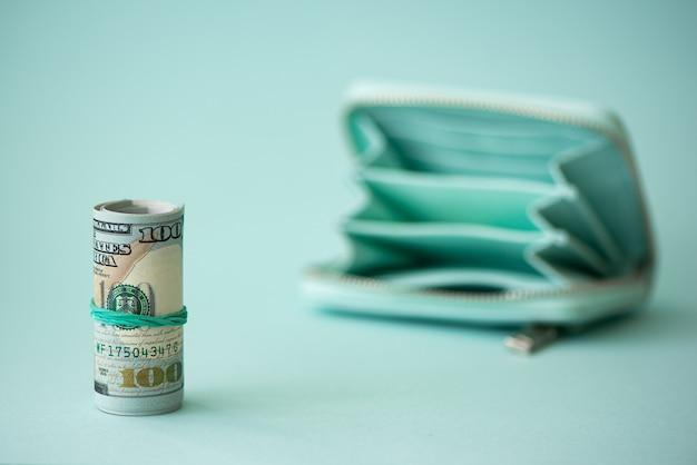 Turkusowy portfel i pieniądze na jasnym tle
