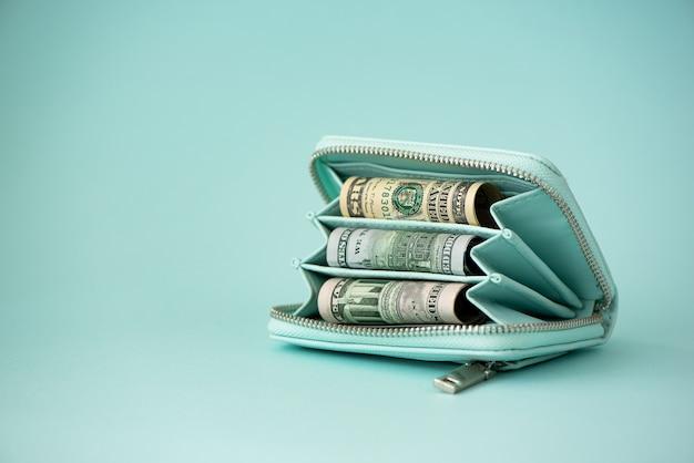Turkusowy portfel z pieniędzmi na jasnym tle