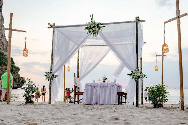 Turyści cieszą się widokiem zachodu słońca na plaży na piasku nakryty stół udekorowany na romantyczną kolację