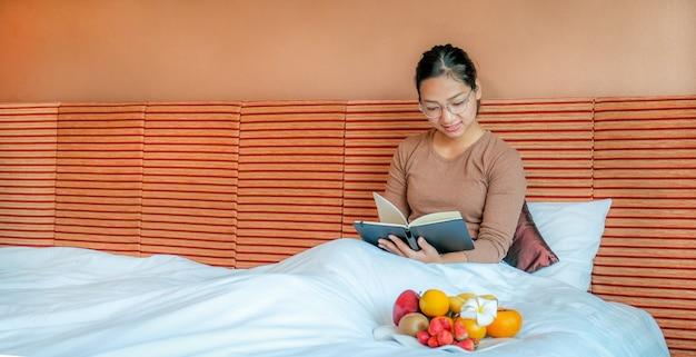 Turyści czytają zeszyty i jedzą owoce na łóżku w luksusowym pokoju hotelowym koncepcja zdrowej żywności