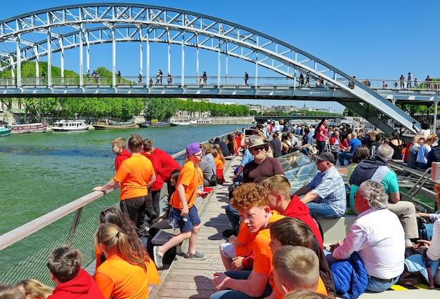 Turyści i nastoletnie dzieci w jasnopomarańczowych koszulkach pływają statkiem wycieczkowym po sein paris