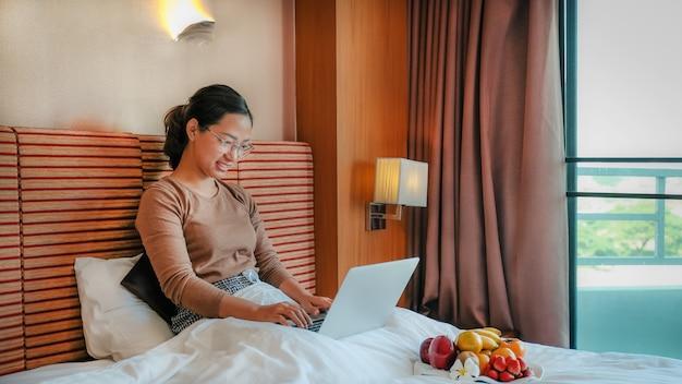 Turyści korzystali z laptopa i jedli owoce na łóżku w luksusowej koncepcji zdrowej żywności w pokoju hotelowym