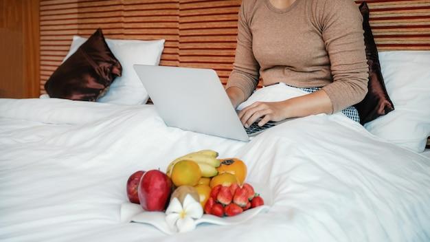 Turyści korzystali z laptopa i jedli owoce na łóżku w luksusowym pokoju hotelowym koncepcja zdrowej żywności