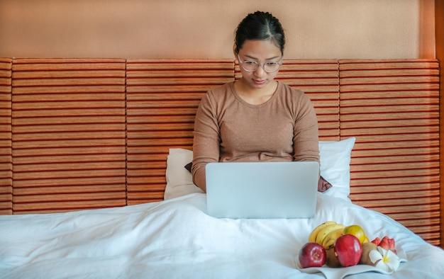 Turyści korzystali z laptopa i jedli owoce na łóżku w luksusowym pokoju hotelowym koncepcji zdrowej żywności