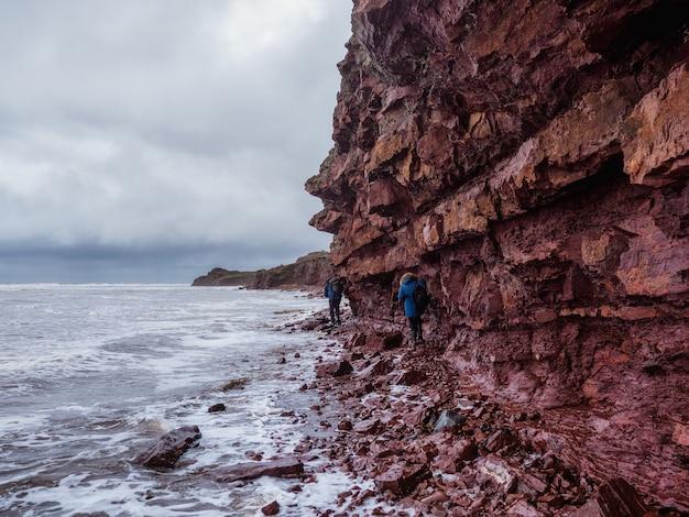 Turyści na klifie nad morzem z wąską linią brzegową.