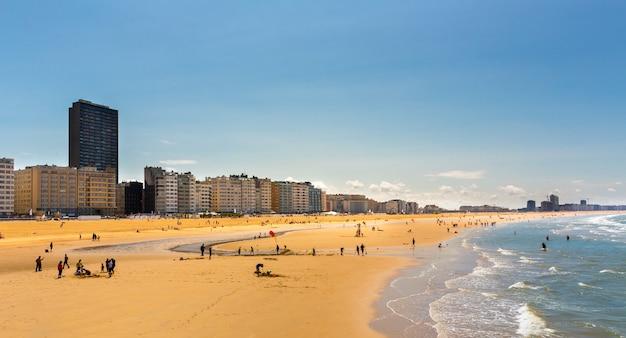 Turyści na plaży miejskiej, wybrzeże morza, europa. turystyka letnia i podróże, znane i lubiane miejsca na wakacje lub wakacje or