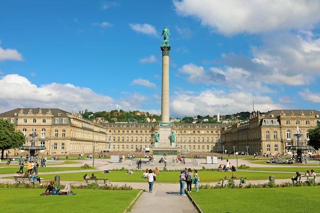 Turyści na schlossplatz z kolumną i nowym pałacem w stuttgarcie w niemczech