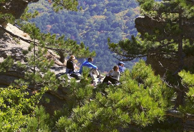 Turyści odpoczywają w górach krymu wśród sosen i drzew w słoneczny dzień. rosja, 2019