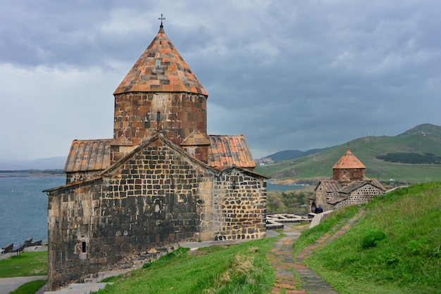 Turyści odwiedzają klasztor sevanavank, położony na półwyspie sevan, wśród jasnozielonych wzgórz
