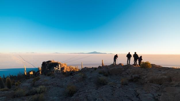 Turyści ogląda wschód słońca przy uyuni salt flat, miejsca przeznaczenia w boliwia.