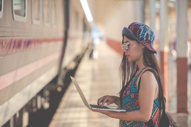 Turyści patrzą na tablet, aby wyszukać atrakcje turystyczne.