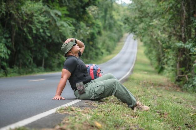 Turyści piesi czekają na autostop lub pomoc na poboczu drogi w lesie parku narodowego khao yai. młodzi turyści płci męskiej przewożących plecak do podróży autostopem. podróżuj autostopem.