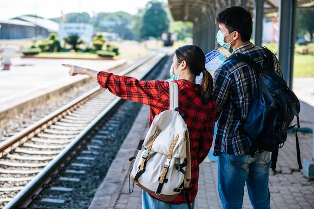 Turyści płci męskiej i żeńskiej patrzą na mapę obok torów kolejowych.